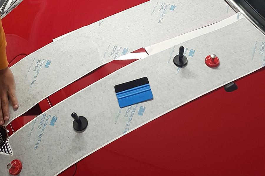 Instalación de vinilo de corte en capó de Mini Cooper rojo